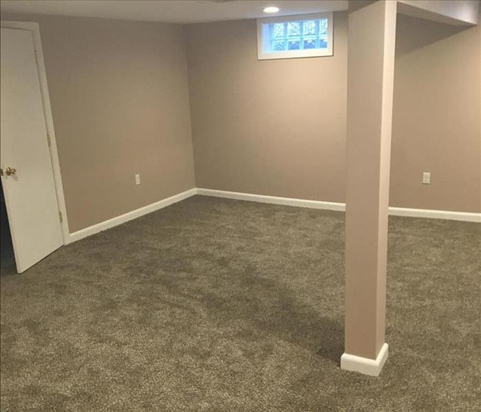 image of the same basement fully carpeted, finished, and painted