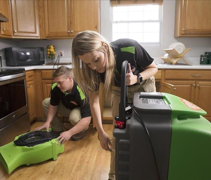 image of SERVPRO water technicians setting up equipment to begin the drying process of water damage to a home
