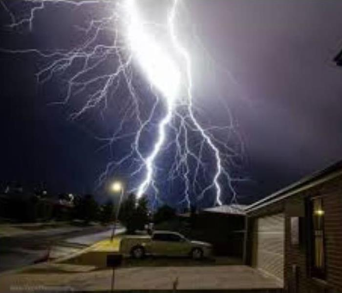 Lightning bolt hits the roof of a home during a thunderstorm