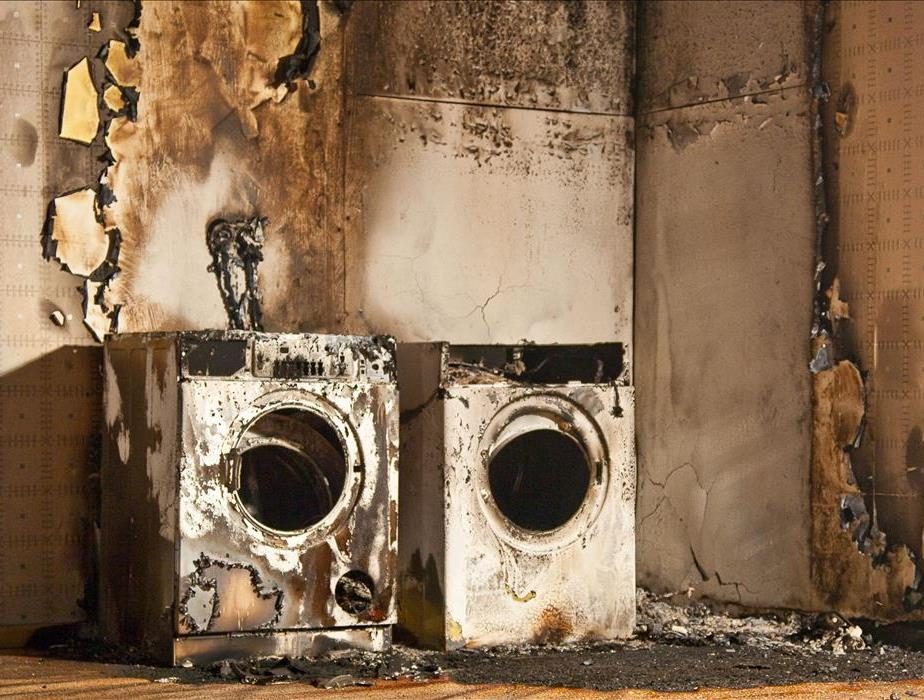 image of dryer machines severely burnt causing significant fire damage to the structure of the property