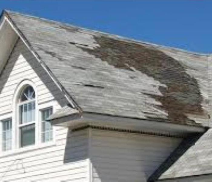 Missing shingles on the roof of a home following a heavy rain storm