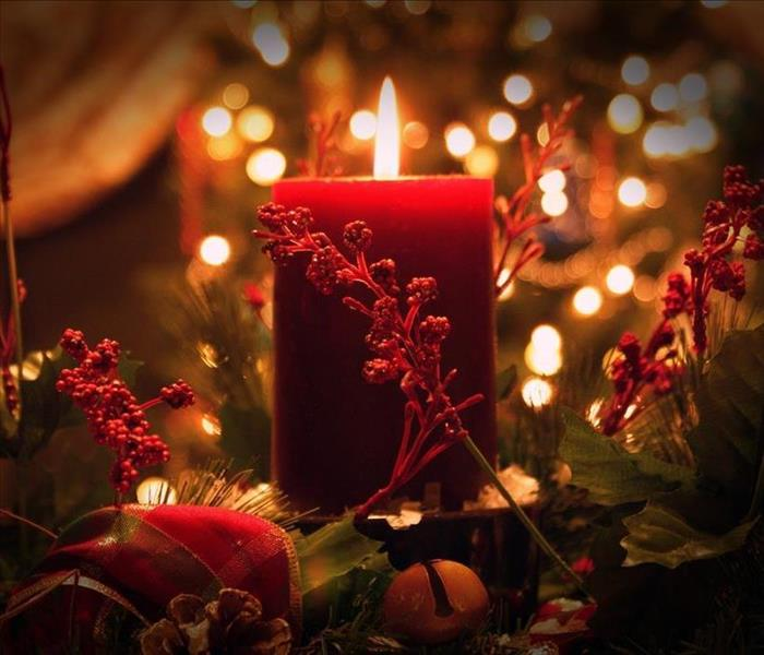 candle with christmas decor surrounding the flame